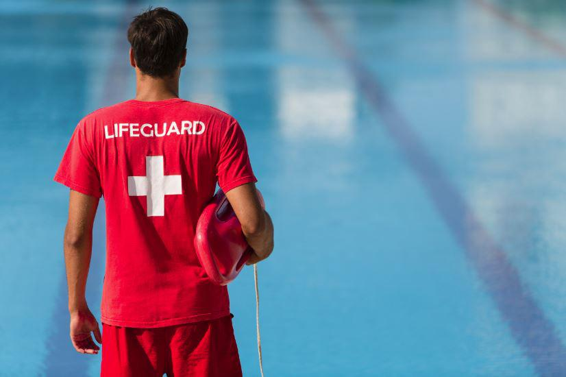 This is an image which shows a man who is a lifeguard and is standing and watching over the pool